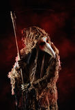 Epidemic. Portrait of a terrible plague doctor with a scythe. Medieval Europe. Horror. Halloween Royalty Free Stock Photos