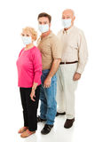 Epidemic - Wearing Face Masks. Elderly couple and their adult son wearing surgical masks to protect against a health epidemic.  Could be swine flu Royalty Free Stock Images