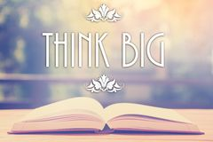 Epigraph over the opened book with elegant ornament - Think big Royalty Free Stock Photo