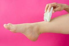 Epilates de la mujer su pierna con un epilator Fotos de archivo libres de regalías