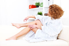 Epilation. Imagine of a young woman shaving her legs with electric shaver at home Royalty Free Stock Photo