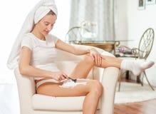 epilation Kvinnan rakar hennes ben hemma royaltyfri foto
