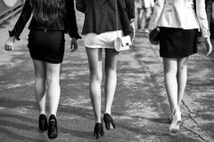 Epilation of the legs. three girls in short skirts. Epilation of the legs. female legs of three young girls on high heels walking in street sunny day with stock image
