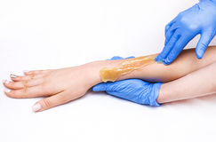 Epilation sugar processes woman passes. In a beauty salon Royalty Free Stock Photography