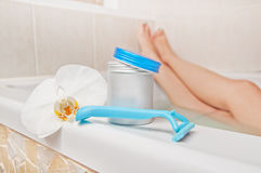 Epilation time - woman legs in bath and shaving accessories. Ski Royalty Free Stock Image