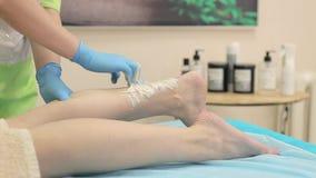 Epilation vax i brunnsortsalongen Kosmetologen lägger på vaxet på kvinnors ben Närbild lager videofilmer