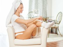 Epilation. Woman epilates her leg with an electric epilator device. At home stock photo
