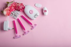 Epilator and disposable razor, next to several buds of beautiful roses. On a pink background. Royalty Free Stock Photography