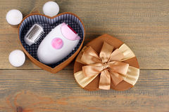 Epilator. While lying down in a box for gift next to a candle on a wooden table Stock Photo