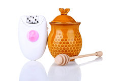Epilator. With a pot of honey and a spoon of honey  on white background Royalty Free Stock Photos