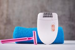 Epilator, shaving razor and bathroom towel. Epilator and shaving razor on background with shampoo and towel, selective focus royalty free stock image
