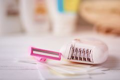 Epilator, shaving razor and wax strips. On background with shampoo and towel, selective focus royalty free stock photo