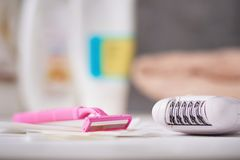 Epilator, shaving razor and wax strips. On background with shampoo and towel, selective focus stock photo