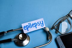 Epilepsy inscription with the view of stethoscope, eyeglasses and smartphone on the blue background. Conceptual image with Epilepsy inscription with the view of royalty free stock image