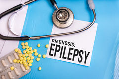 Epilepsy word written on medical blue folder with patient files. Pills and stethoscope on background stock images