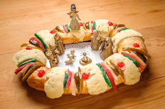 Epiphany cake, kings cake, or rosca de reyes. With manger on wooden table Stock Photo