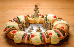 Epiphany cake, kings cake, or rosca de reyes. With manger on wooden table Royalty Free Stock Image