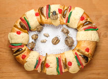 Epiphany cake, Kings cake, Rosca de reyes or Roscon de reyes. Epiphany Cake, kings cake, or Rosca de reyes with manger on wooden table top view royalty free stock photography