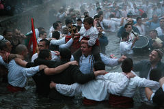 Epiphany Traditions - Jordan. Men dance in the icy waters of the river Tunja on January 6, 2011, Kalofer, Bulgaria. Kalofer, Bulgaria - January 6, 2011: People Royalty Free Stock Photo