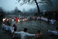 Epiphany Traditions - Jordan. Men dance in the icy waters of the river Tunja on January 6, 2011, Kalofer, Bulgaria. Kalofer, Bulgaria - January 6, 2011: People Stock Photo