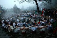 Epiphany Traditions - Jordan. Men dance in the icy waters of the river Tunja on January 6, 2011, Kalofer, Bulgaria. Kalofer, Bulgaria - January 6, 2011: People Stock Photography