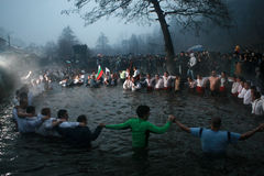 Epiphany Traditions - Jordan. Men dance in the icy waters of the river Tunja on January 6, 2011, Kalofer, Bulgaria. Kalofer, Bulgaria - January 6, 2011: People Stock Images