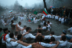 Epiphany Traditions - Jordan. Men dance in the icy waters of the river Tunja on January 6, 2011, Kalofer, Bulgaria royalty free stock images