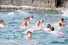 Epiphany (Vodici, Bogojavlenje) in Macedonia. STRUGA, MACEDONIA - JANUARY 19, 2012: Men jump into the cold water to retrieve the cross at the Epiphany (Vodici Royalty Free Stock Photo