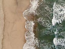 Epische vertikale Luftbrummenansicht der Wellenbewegung auf mehrfarbigem sandigem Strand lizenzfreie stockbilder