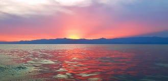 Episk röd solnedgångplats över havet i Rwanda, East Africa, sol reflekterad på vatten royaltyfria foton