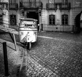 Episodes and stories of the old Lisbon. Portugal. Black and white. Tuk-Tuk on the streets of old Lisbon royalty free stock photos