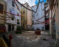 Episodes and stories of the yards of the old Lisbon. Portugal. Courtyards of Lisbon. Simple life without a beauty. Paving stone on the streets of the city royalty free stock image