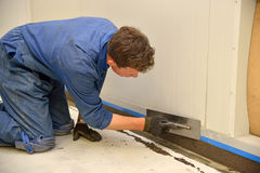Epoxy surface for floor. Tradesman applying epoxy product to coving around the floor of an industrial building Royalty Free Stock Image