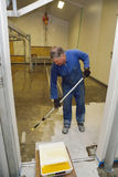 Epoxy surface for floor. Tradesman applying epoxy product to floor of an industrial building Stock Images