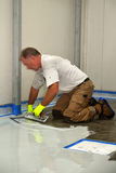 Epoxy surface for floor. Tradesman applying epoxy product to floor of an industrial building Royalty Free Stock Photo