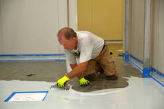 Epoxy surface for floor. Tradesman applying epoxy product to floor of an industrial building Stock Photos