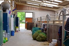 Inside of riding stable with empty horse stalls stock photos
