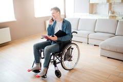 Νεαρός άνδρας στην αναπηρική καρέκλα Άτομο με ειδικές ανάγκες Ανικανότητα Συνεδρίαση σπουδαστών και ομιλία στο τηλέφωνο Εκμετάλλε στοκ φωτογραφίες