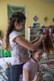 Νέο κορίτσι που πλέκει την τρίχα φίλων της Χαμογελώντας κορίτσι κατά τη διάρκεια της τρίχας πλεξίματος Επιλεγμένη εστίαση στοκ φωτογραφία με δικαίωμα ελεύθερης χρήσης