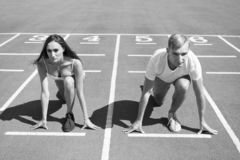 Equal forces concept. Man and woman low start position running surface stadium. Running competition or gender race. Equal forces concept. Man and women low start stock photo