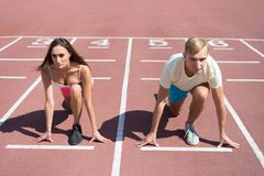 Equal forces concept. Man and woman low start position running surface stadium. Running competition or gender race. Equal forces concept. Man and women low start royalty free stock photography
