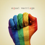 Equal marriage. Text equal marriage and a man hand patterned with the rainbow flag on a beige background Stock Photos