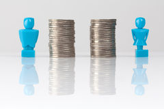 Equal pay concept shown with figurines and coins Stock Image