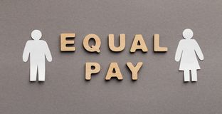 Equal Pay for man and woman concept. Equal Pay for man and woman, wooden words with gender figures on gray background, panorama royalty free stock photography