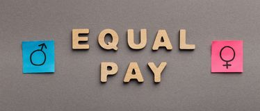 Equal Pay for man and woman concept. Equal Pay for man and woman, wooden words with gender symbols on gray background, panorama stock image