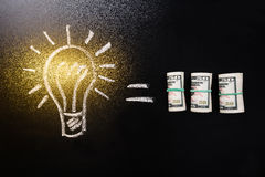 Equal Sign Between Light Bulb And Currency Note Royalty Free Stock Photography