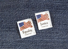 Equality and Justice Forever. Two Forever Stamps promoting Equality and Justice against blue denim royalty free stock photo