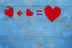 Equation with hearts arranged on blue background Stock Image
