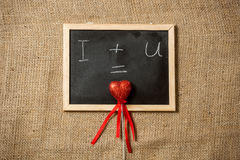 Equation of love written on blackboard with red heart Royalty Free Stock Photo