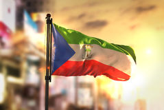 Equatorial Guinea Flag Against City Blurred Background At Sunris Royalty Free Stock Photography